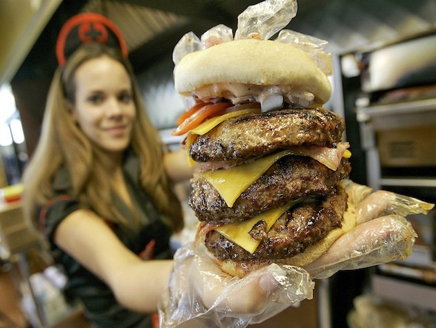 Courtney Chapman, a waitress dressed as a nurse at the Heart Attack Grill, holds up a triple bypass burger Friday, Dec. 1, 2006 in Tempe, Ariz. The waitresses at the restaurant, who wear minimal nurses attire, have angered a group of real Arizona nurses who say the servers demean their profession. (AP Photo/Matt York)