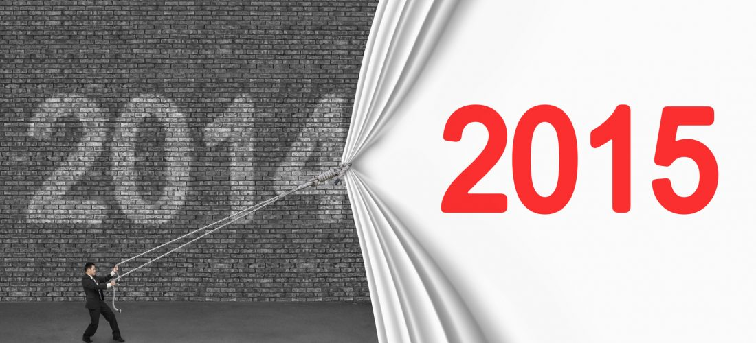 businessman pulling down 2015 curtain covering old 2014 brick wall